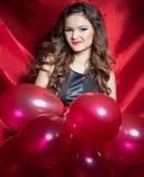 Mujer joven feliz elegante hermosa con las bolas rojas en manos con el lápiz labial rojo Imagen de archivo