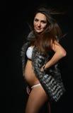 Mujer joven feliz embarazada con el pelo ventoso en un fondo negro Imágenes de archivo libres de regalías