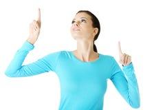 Mujer joven feliz, emocionada que señala en espacio de la copia Fotos de archivo