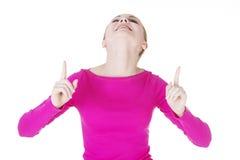 Mujer joven feliz, emocionada que señala en espacio de la copia Imagenes de archivo