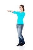 Mujer joven feliz, emocionada que señala en espacio de la copia Fotografía de archivo libre de regalías