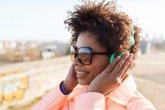 Mujer joven feliz en auriculares que escucha la música Foto de archivo libre de regalías