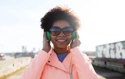 Mujer joven feliz en auriculares que escucha la música Foto de archivo