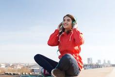 Mujer joven feliz en auriculares que escucha la música Imagen de archivo