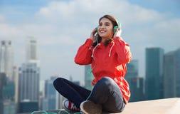 Mujer joven feliz en auriculares que escucha la música Imágenes de archivo libres de regalías