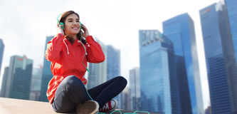 Mujer joven feliz en auriculares que escucha la música Fotografía de archivo libre de regalías