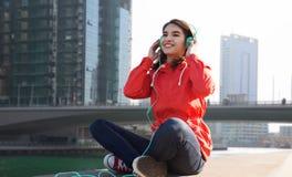 Mujer joven feliz en auriculares que escucha la música Fotos de archivo