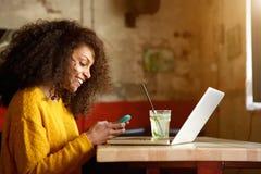 Mujer joven feliz en cafetería usando el teléfono móvil Imagen de archivo