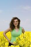 Mujer joven feliz en campo de flor de la violación Imagen de archivo