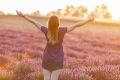 Mujer joven feliz en campo de la lavanda en la puesta del sol foto de archivo libre de regalías
