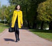 Mujer joven feliz en capa amarilla en calle del otoño Imagenes de archivo