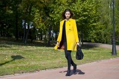 Mujer joven feliz en capa amarilla en calle del otoño Imagen de archivo libre de regalías