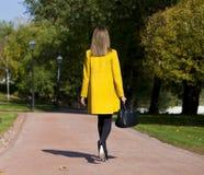 Mujer joven feliz en capa amarilla en calle del otoño Foto de archivo libre de regalías