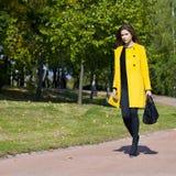 Mujer joven feliz en capa amarilla en calle del otoño Fotografía de archivo libre de regalías