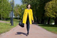 Mujer joven feliz en capa amarilla en calle del otoño Imagen de archivo