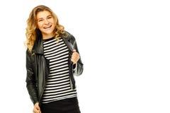 Mujer joven feliz en chaqueta de cuero negra sobre el fondo blanco Imágenes de archivo libres de regalías