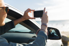 Mujer joven feliz en coche con smartphone en el mar Imágenes de archivo libres de regalías