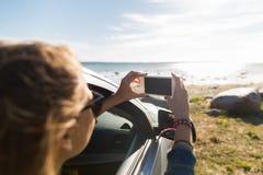 Mujer joven feliz en coche con smartphone en el mar Fotografía de archivo libre de regalías