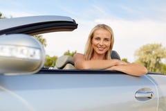 Mujer joven feliz en coche convertible imagen de archivo libre de regalías