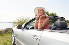 Mujer joven feliz en coche convertible foto de archivo