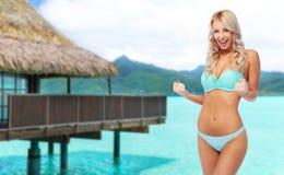 Mujer joven feliz en el bikini que hace la bomba del pu?o imagenes de archivo