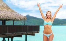 Mujer joven feliz en el bikini que hace la bomba del pu?o imagen de archivo libre de regalías