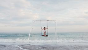 Mujer joven feliz en el montar a caballo blanco del traje de baño en el oscilación que disfruta de la opinión del mar Concepto de almacen de video