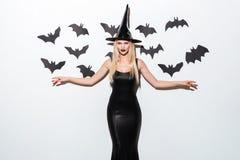 Mujer joven feliz en el negro que traje de Halloween con el sombrero Imagen de archivo libre de regalías