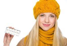 Mujer joven feliz en el paquete de la demostración del sombrero y de la bufanda de píldoras Fotos de archivo libres de regalías