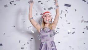 Mujer joven feliz en el sombrero de Papá Noel en el partido de la celebración con caer del confeti metrajes
