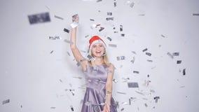 Mujer joven feliz en el sombrero de Papá Noel en el partido de la celebración con caer del confeti almacen de metraje de vídeo