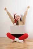 Mujer joven feliz en el sombrero de santa que busca los presentes en línea para Chr fotografía de archivo libre de regalías