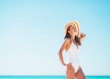 Mujer joven feliz en el sombrero del traje de baño y de la playa que se relaja en la playa Fotos de archivo libres de regalías