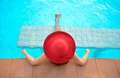Mujer joven feliz en el sombrero grande rojo que se relaja en la piscina, el viaje cerca del mar y la playa Fotografía de archivo