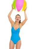 Mujer feliz en el traje de baño que juega con la pelota de playa Fotografía de archivo libre de regalías