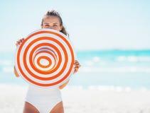 Mujer joven feliz en el traje de baño que oculta detrás del sombrero de la playa Fotos de archivo