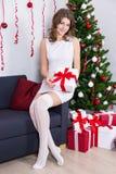 Mujer joven feliz en el vestido blanco con el árbol de navidad adornado Fotografía de archivo libre de regalías