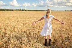 Mujer joven feliz en el vestido blanco en campo de cereal Fotos de archivo libres de regalías