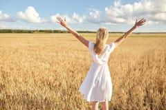 Mujer joven feliz en el vestido blanco en campo de cereal Imagenes de archivo