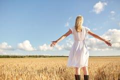 Mujer joven feliz en el vestido blanco en campo de cereal Imagen de archivo libre de regalías