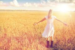 Mujer joven feliz en el vestido blanco en campo de cereal Foto de archivo libre de regalías