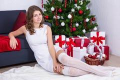Mujer joven feliz en el vestido blanco que se sienta cerca de Christma adornado Imagenes de archivo