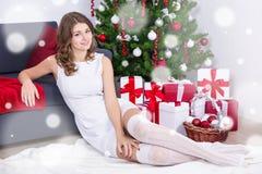 Mujer joven feliz en el vestido blanco que se sienta cerca de Christma adornado Imágenes de archivo libres de regalías
