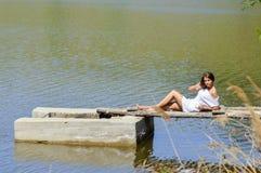 Mujer joven feliz en el vestido blanco que se sienta en el embarcadero por el río o el lago Imagenes de archivo
