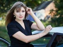 11869c5759 Mujer joven feliz en el vestido negro de moda que presenta con el coche  Conductor de