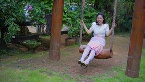 Mujer joven feliz en el vestido tradicional tailandés que se relaja en un oscilación de madera metrajes