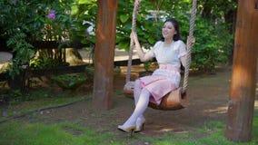 Mujer joven feliz en el vestido tradicional tailandés que se relaja en un oscilación de madera almacen de metraje de vídeo