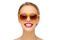 Mujer joven feliz en gafas de sol con el lápiz labial rosado Imagen de archivo