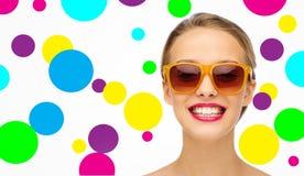 Mujer joven feliz en gafas de sol con el lápiz labial rosado Foto de archivo libre de regalías