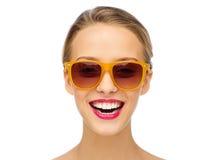 Mujer joven feliz en gafas de sol con el lápiz labial rosado Fotografía de archivo